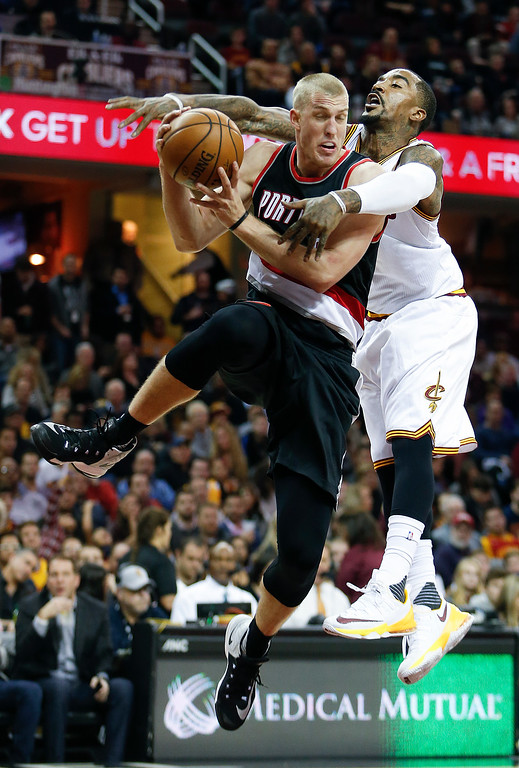 . Portland Trail Blazers\' Mason Plumlee (24) gets fouled going up for a shot by Cleveland Cavaliers\' J.R. Smith (5) during the second half of an NBA basketball game Wednesday, Nov. 23, 2016, in Cleveland. The Cavaliers won 137-125. (AP Photo/Ron Schwane)