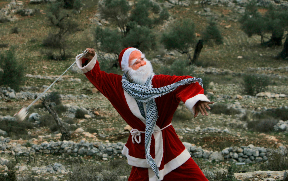 Description of . A Palestinian demonstrator dressed as Santa Claus uses a sling-shot to hurl stones at Israeli border police during a demonstration against Israel's separation barrier in the West Bank village of Bilin near Ramallah, Friday, Dec. 26, 2008. Israel says the barrier is necessary for security while Palestinians call it a land grab.(AP Photo/Muhammed Muheisen)