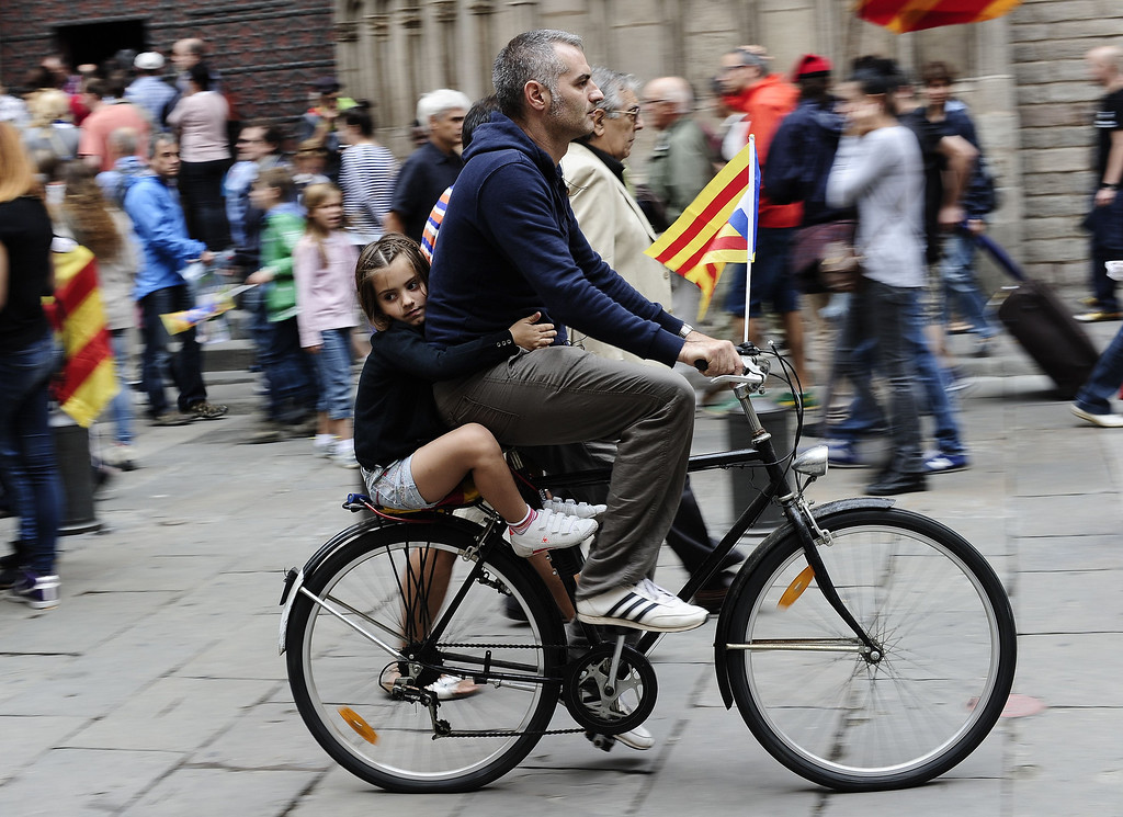 """. A child rides as a passenger on a bike sporting Catalonia\'s flag \""""Estelada\"""" during celebrations for Catalonia National Day, or Diada, in Barcelona on September 11, 2013. Independence-seeking Catalans marshalled their forces today in a bid to create a 400-kilometre (250-mile) human chain they say will stretch across 86 cities, towns and villages along the coast of the northeastern region on the Mediterranean, passing landmarks such as the Sagrada Familia basilica in Barcelona and the city\'s Camp Nou football stadium. JOSEP LAGO/AFP/Getty Images"""