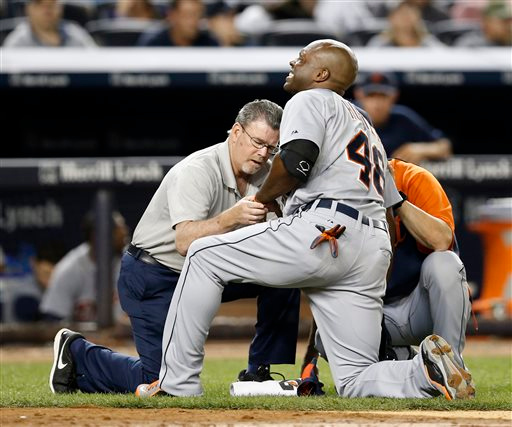 . Detroit Tigers\' Torii Hunter (48) is examined by a trainer after he was hit in the hand by a pitch thrown by New York Yankees\' Dellin Betances in the ninth inning of a baseball game at Yankee Stadium in New York, Tuesday, Aug. 5, 2014. (AP Photo/Kathy Willens)