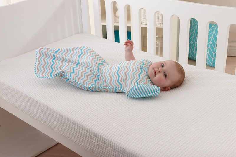 Love_To_Dream_Stage_2_5050_Zigzag_Turquoise_Lifestyle_Side_View_In_Cot_Arm_Up.jpg
