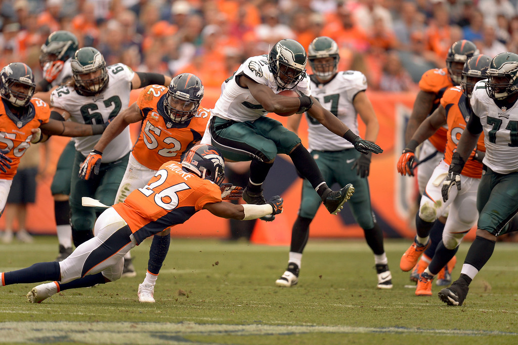 . DENVER, CO - SEPTEMBER 29: Philadelphia Eagles running back LeSean McCoy (25) leaps over Denver Broncos free safety Rahim Moore (26) for a short gain during the third quarterSeptember 29, 2013 at Sports Authority Field at Mile High (Photo by John Leyba/The Denver Post)