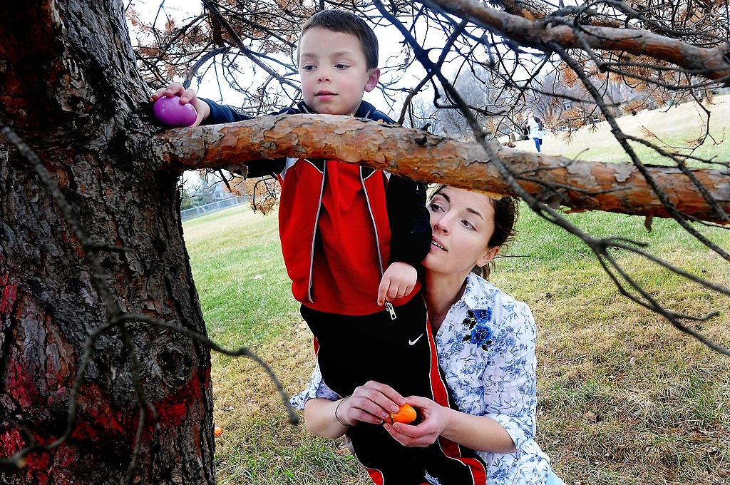 . In St. Paul\'s Dayton\'s Bluff neighborhood, Samuel Woolley, 5, is held by his mother, Erin Brown, as they hide Easter eggs while volunteering for Mounds Park United Methodist Church as they prep 30 minutes prior to the annual Easter egg hunt at Indian Mounds Park. (Pioneer Press: Sherri LaRose-Chiglo)