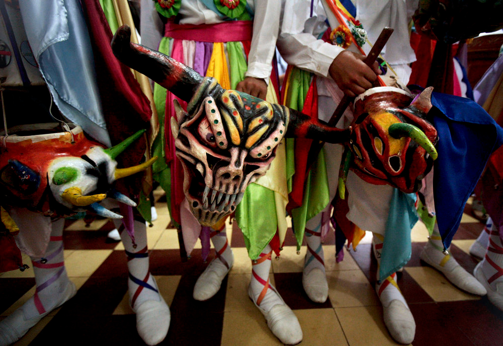 . Men hold traditional devil masks during Corpus Christi mass celebrations at the San Atanacio church in La Villa, Panama, Thursday, May 30, 2013. Residents don colorful masks and bright costumes as they dance through the streets of this small Panamanian town, for its annual commemoration of Corpus Christi, a Roman Catholic holiday celebrating the transformation of the body and blood of Christ into bread and wine. (AP Photo/Arnulfo Franco)
