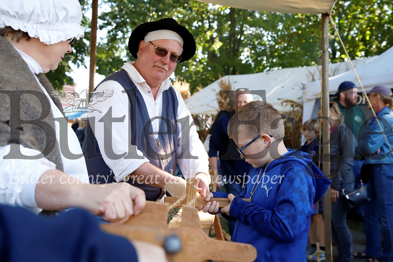 Blake Wright, 10, works on making rope at Bob and Carol Huber's colonial wood crafts booth at Zelienople Fall Festival Saturday. Seb Foltz/Butler Eagle 2019