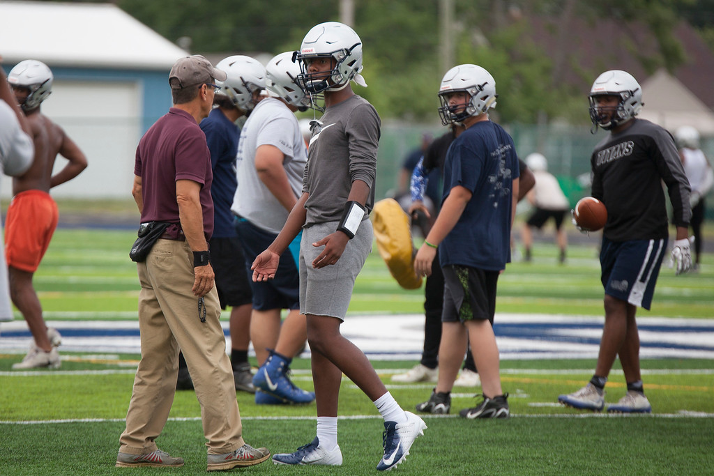 . Jen Forbus - The Morning Journal<br> Lorain coach Dave McFarland confers with quarterback Jordan Jackson during Lorain\'s first football practice on July 30.