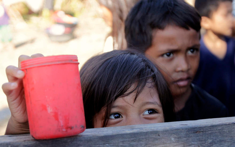 . Children wait for free porridge distributed outside an evacuation centre for residents who were rendered homeless after their houses were swept by floodwaters at the height of Typhoon Bopha, in New Bataan town in Compostela Valley, southern Philippines December 8, 2012. Philippine President Benigno Aquino declared a state of national calamity on Saturday, four days after this year\'s strongest typhoon left nearly 1,000 people dead or missing mostly in the country\'s resource-rich south. REUTERS/Erik De Castro