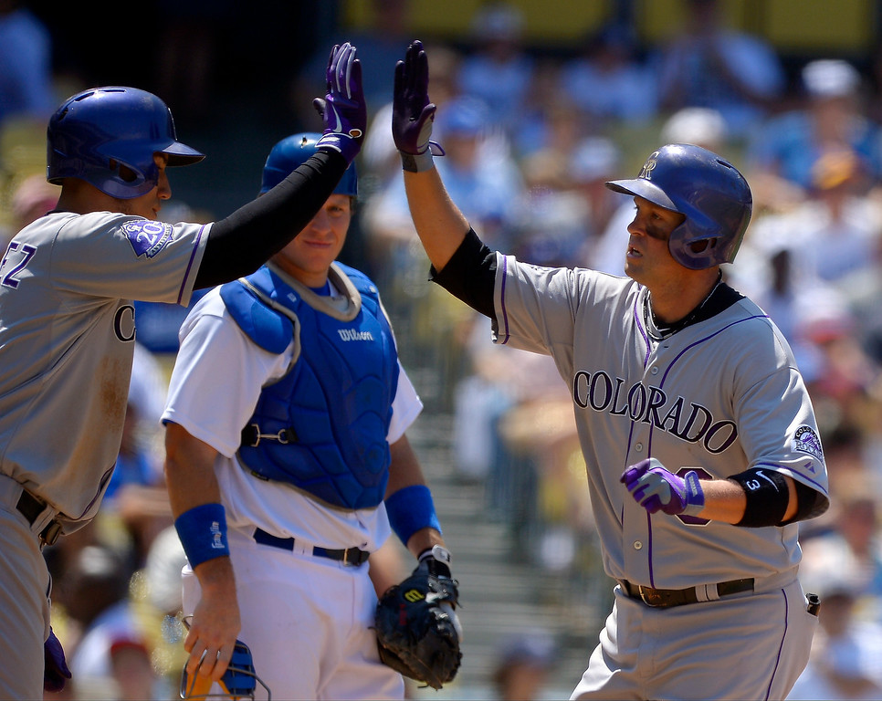 . As Los Angeles Dodgers catcher A.J. Ellis, center, looks on Colorado Rockies\' Michael Cuddyer, right, is congratulated by teammate Carlos Gonzalez, left,  after hitting a two-run home run during the fifth inning of their baseball game on Sunday, July 14, 2013, in Los Angeles. (AP Photo/Mark J. Terrill)