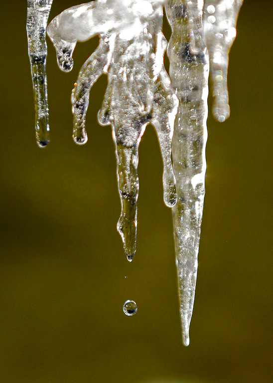 . A droplet of water falls from an icicle on a partially frozen fountain, Wednesday, Jan. 4, 2017, in Tacoma, Wash. Wet winter weather slammed much of the West on Wednesday, with storms dropping several inches of snow on one Oregon city and several feet of the white stuff predicted high in the Sierra Nevada. (AP Photo/Ted S. Warren)