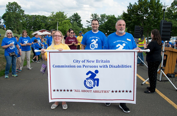 07/24/19 Wesley Bunnell | Staff Commissioner Alicia Rutkowski, L, and Commissioner Alden Russell, R, carry a banner at the start of the Walk and Roll on Wednesday afternoon at Walnut Hill Park. The Walk and Roll is hosted by the citys Commission on Persons with Disabilities and celebrates the signing of the American with Disabilities Act of 1990 and serves to raise awareness for improving the quality of life for all residents in the city, regardless of disability.