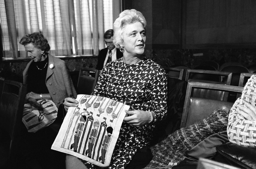 . Mrs. Barbara  Bush, wife of the man nominated to head the central Intelligence Agency looks up from her needlepoint as her husband prepares to begin his testimony before the Senate Armed Services Committee on Monday, Dec. 16, 1975 in Washington. Bush, currently the official U.S. representative to the People?s Republic of China, appeared before the panel which is considering his nomination to the intelligence post. (AP Photo/CWH)