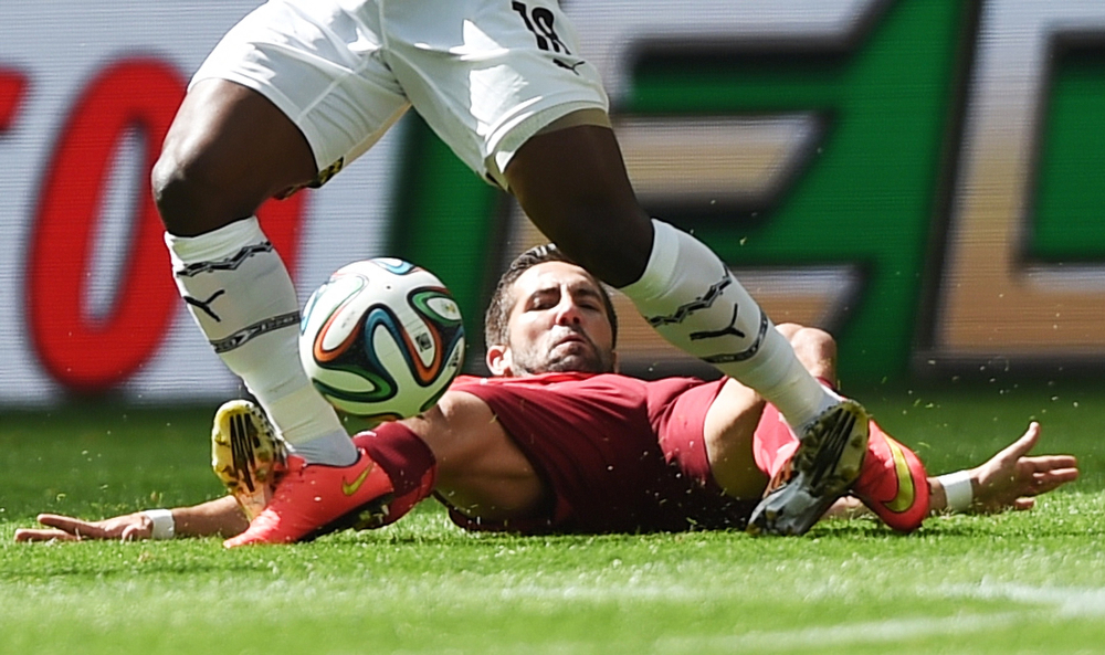 . Ghana\'s forward Abdul Majeed Waris (top) and Portugal\'s midfielder Joao Moutinho vie during the Group G football match between Portugal and Ghana at the Mane Garrincha National Stadium in Brasilia during the 2014 FIFA World Cup on June 26, 2014.  (FRANCISCO LEONG/AFP/Getty Images)