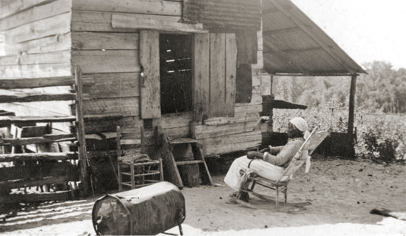 """. Old Aunt Julia Ann Jackson, age 102 and the corn crib where she lives. Between 1937 and ca. 1938. She uses the large battered tin can for a stove and does her cooking on it. Aunt Julia Ann is an ex-slave and was grown woman when the Civil \""""Wah broke out.\"""" Library of Congress"""