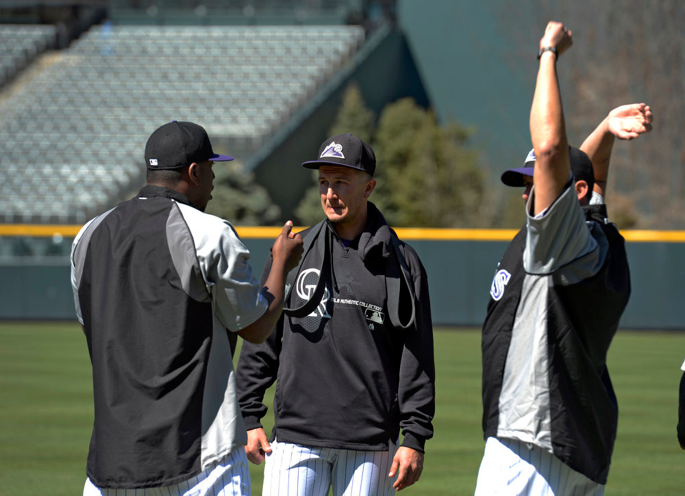 . Juan Nicasio (L) talks with Troy Tulowitzki (M) and Rafael Betancourt  after an argument broke out between Nicasio and Escolona during stretching exercises. Manager Walt Weiss talked with both pitchers after practice. The Colorado Rockies held an open practice for the fans April 4, 2013 at Coors Field. (Photo By John Leyba/The Denver Post)