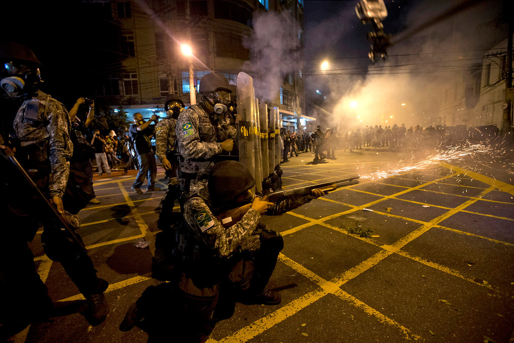 . Military police fire tear gas at protestors near Maracana stadium where Brazil and Spain are playing the final Confederations Cup soccer match in Rio de Janeiro, Brazil, Sunday, June 30, 2013. Anti-government protesters marched near the Maracana football stadium during the major international match, venting their anger about the billions of dollars the Brazilian government is spending on major sporting events rather than public services. (AP Photo/Silvia Izquierdo)
