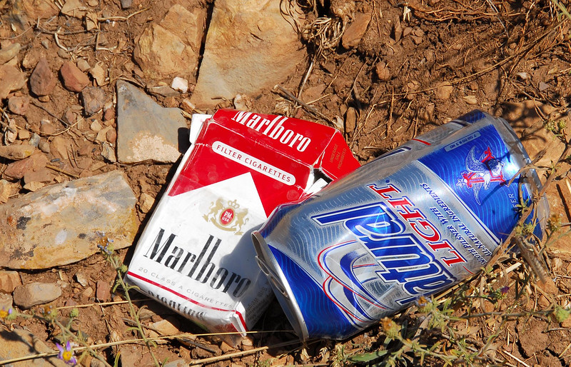 """9/28/07 – I call this """"Vice Trash."""" Someone had their last cigarette and finished their beer and then just left their trash on the ground. I didn't move or arrange these items. I found them just like this in an open area. It made me wonder who was there and why."""