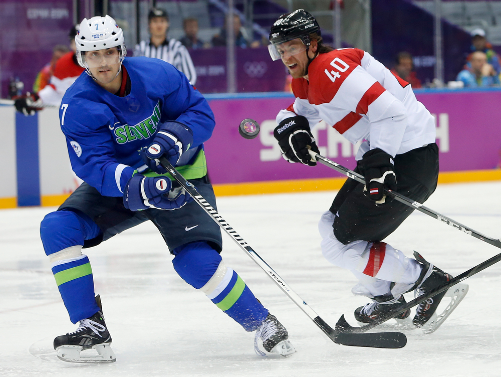 . Slovenia defenseman Klemen Pretnar takes a pass as Austria forward Michael Rene Grabner pursues in the third period of a men\'s ice hockey game at the 2014 Winter Olympics, Tuesday, Feb. 18, 2014, in Sochi, Russia. (AP Photo/Mark Humphrey)
