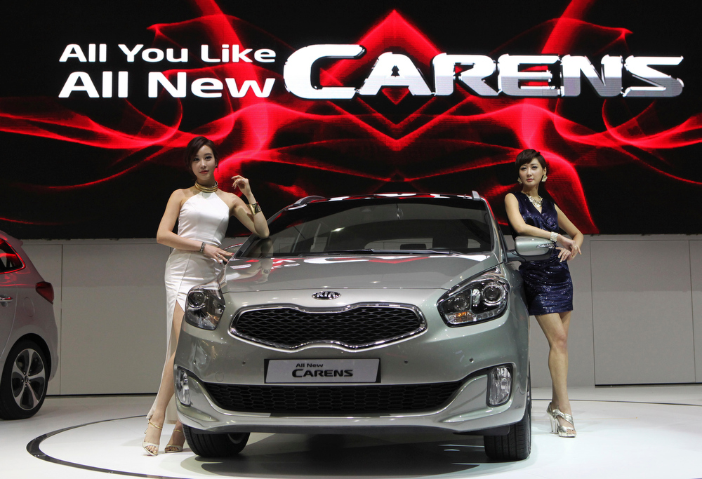. South Korean models pose with Kia Motors\' All New Carens during a press day of the Seoul Motor Show in Goyang, South Korea, Thursday, March 28, 2013. The exhibition, with 384 companies from 14 countries to participate, will be held from March 29 through April 7. (AP Photo/Ahn Young-joon)