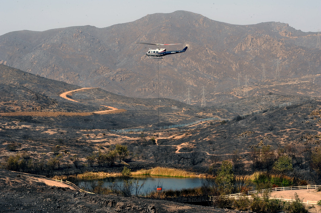. A helicopter drops a water bucket in a pond surrounded by burnt hills in Newbury Park from the Springs Fire, Saturday, May 4, 2013. (Michael Owen Baker/Staff Photographer)
