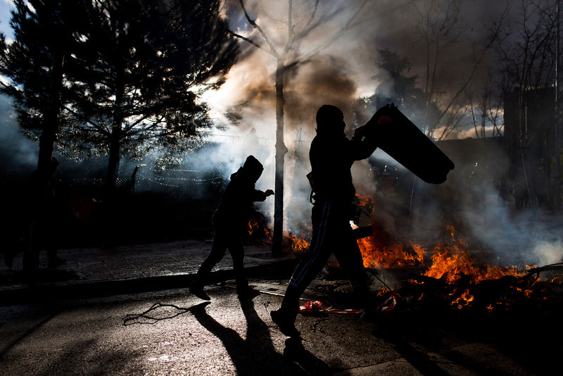 . Students set fire and make barricades, during the first day of a student strike to protest a government education reform and cutbacks in grants and staffing, at Complutense University, in  Madrid, Spain, Wednesday, March 26, 2014. Spanish police say they have arrested more than 50 students when the police moved in to end the occupation of a campus building after the university had asked them to intervene. Students, many with their faces covered, set fire to trash containers and set up barricades on at least two streets in the university complex during the protest. (AP Photo/Andres Kudacki)