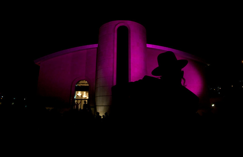 . An Ultra Orthodox Jewish man stands in front of a Synagogue during a celebration in the West Bank Jewish settlement of Modiin Illit, Monday, March 11, 2013. Thousands celebrated the inauguration of a new Torah scroll. (AP Photo/Sebastian Scheiner)