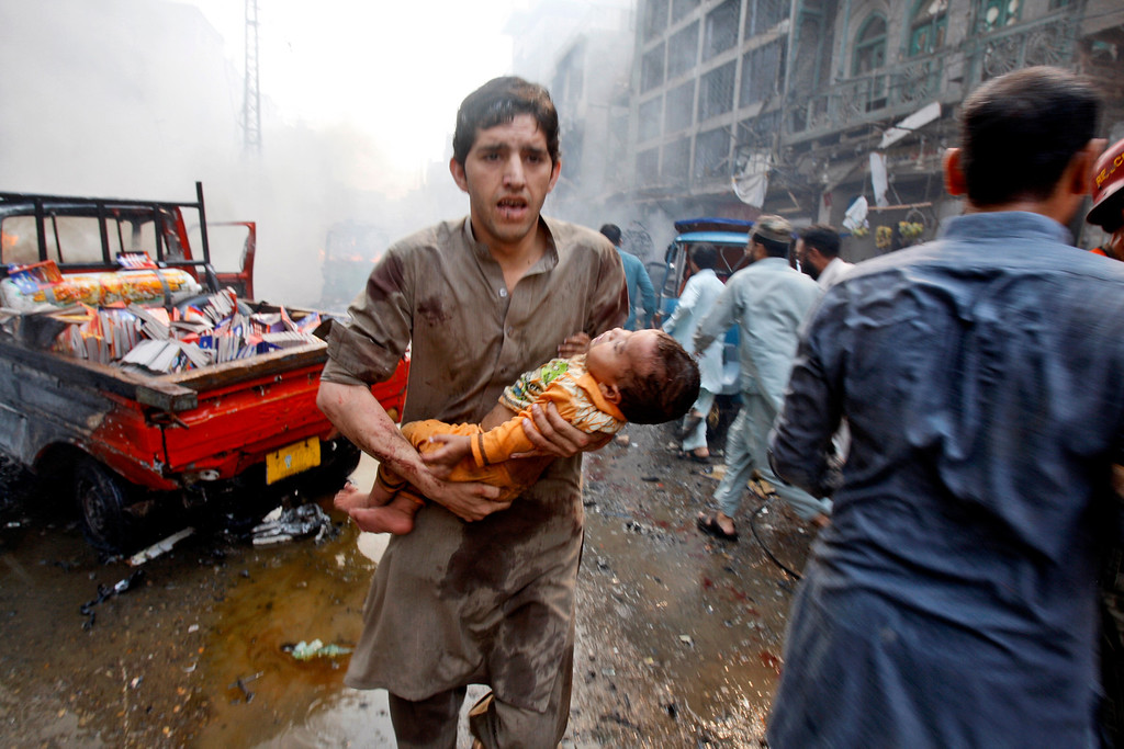 . A Pakistani man carry an injured child away from the site of a car bomb attack in Peshawar, Pakistan, Sunday, Sept. 29, 2013. (AP Photo/Mohammad Sajjad)
