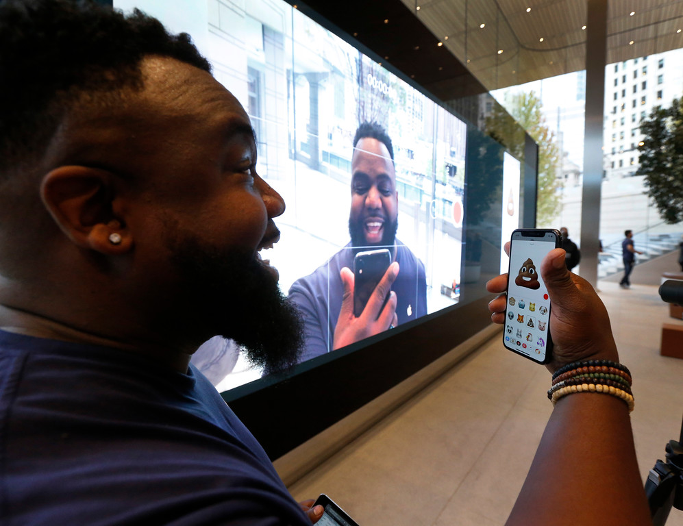 . Apple employee Kenny Johnson tries out one of 12 Animojis that can mirror 50 different muscle movements in the Apple iPhone X at the new Apple Michigan Avenue store along the Chicago River Friday, Nov. 3, 2017, in Chicago. (AP Photo/Charles Rex Arbogast)