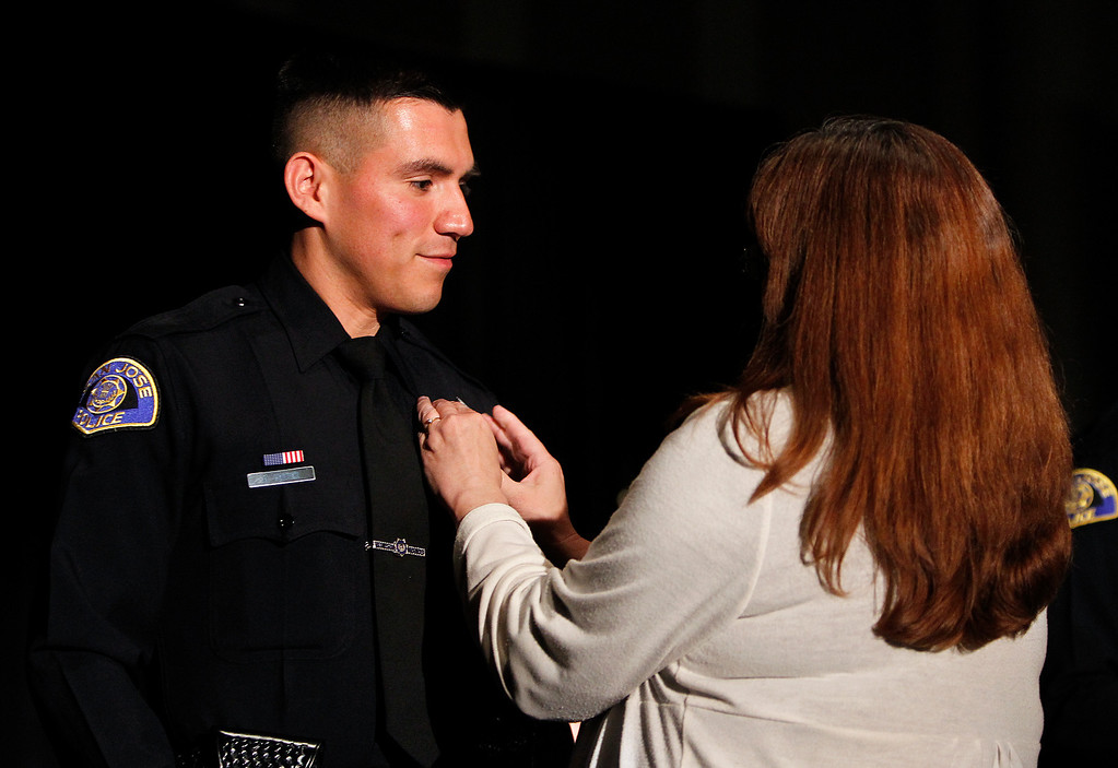 . At left,  San Jose Police Academy Class President David Cortez has his police badge pinned on during the San Jose Police Academy graduation in San Jose, Calif. on Friday, March 15, 2013.   (LiPo Ching/Staff)