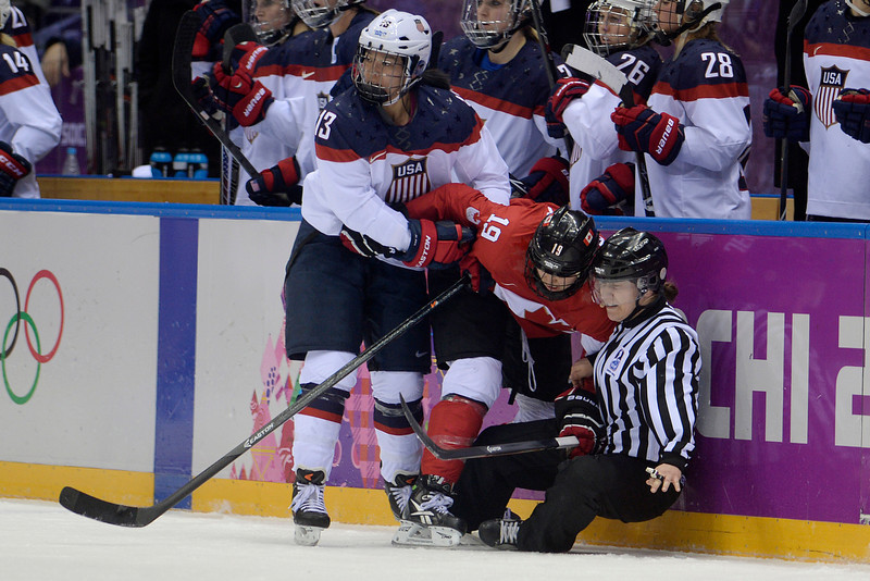 . Julie Chu (13) of the U.S.A. checks Brianne Jenner (19) of the Canada into the referee during the second period of the women\'s gold medal ice hockey game. Sochi 2014 Winter Olympics on Thursday, February 20, 2014 at Bolshoy Ice Arena. (Photo by AAron Ontiveroz/ The Denver Post)