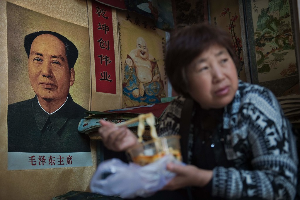 . A vendor eats noodles next to a poster of late Chinese chairman Mao Zedong (L) at a market in Beijing on May 15, 2016. Fifty years after the Cultural Revolution spread bloodshed and turmoil across China, the Communist-ruled country is driving firmly down the capitalist road, but Mao Zedong\'s legacy remains -- like the embalmed leader himself -- far from buried. NICOLAS ASFOURI/AFP/Getty Images