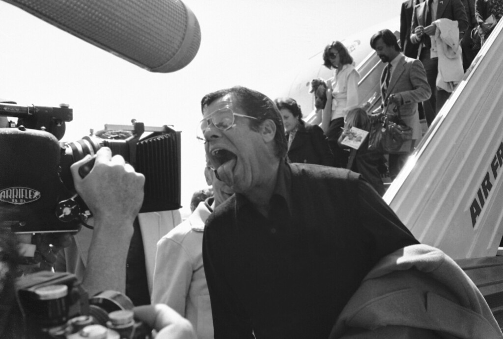 . American Actor Jerry Lewis, center, puts out his tongue as he arrives from New York at Nice Airport on his road to Cannes Film Festival, May 22, 1979, Paris, France. (AP Photo/Jean Jacques Levy)
