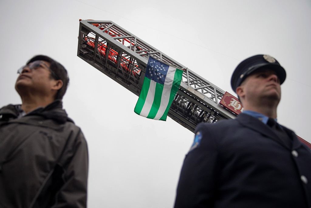. A New York Police Department flag hangs from a FDNY ladder during the funeral of NYPD Officer Wenjian Liu at Aievoli Funeral Home, Sunday, Jan. 4, 2015, in the Brooklyn borough of New York. Liu and his partner, officer Rafael Ramos, were killed Dec. 20 as they sat in their patrol car on a Brooklyn street. The shooter, Ismaaiyl Brinsley, later killed himself. (AP Photo/John Minchillo)