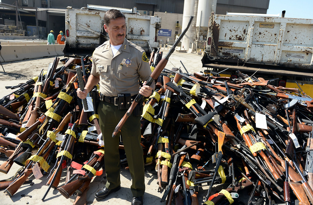 . Los Angeles County Assistant Sheriff Todd Rogers holds a confiscated rifle next to a pile of weapons at Gerdau Steel Mill in Rancho Cucamonga Wednesday August 13, 2014. Approximately 4,700 weapons confiscated amongst 12 Los Angeles County law enforcement agencies were melted down into steel.   (Will Lester/Inland Valley Daily Bulletin)