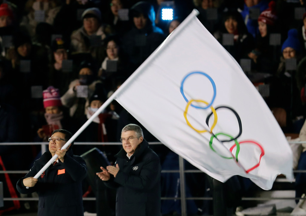 . Chen Jining, mayor of Beijing, waves the Olympic flag as Thomas Bach, president of the International Olympic Committee watches during the closing ceremony of the 2018 Winter Olympics in Pyeongchang, South Korea, Sunday, Feb. 25, 2018. (AP Photo/Michael Probst)