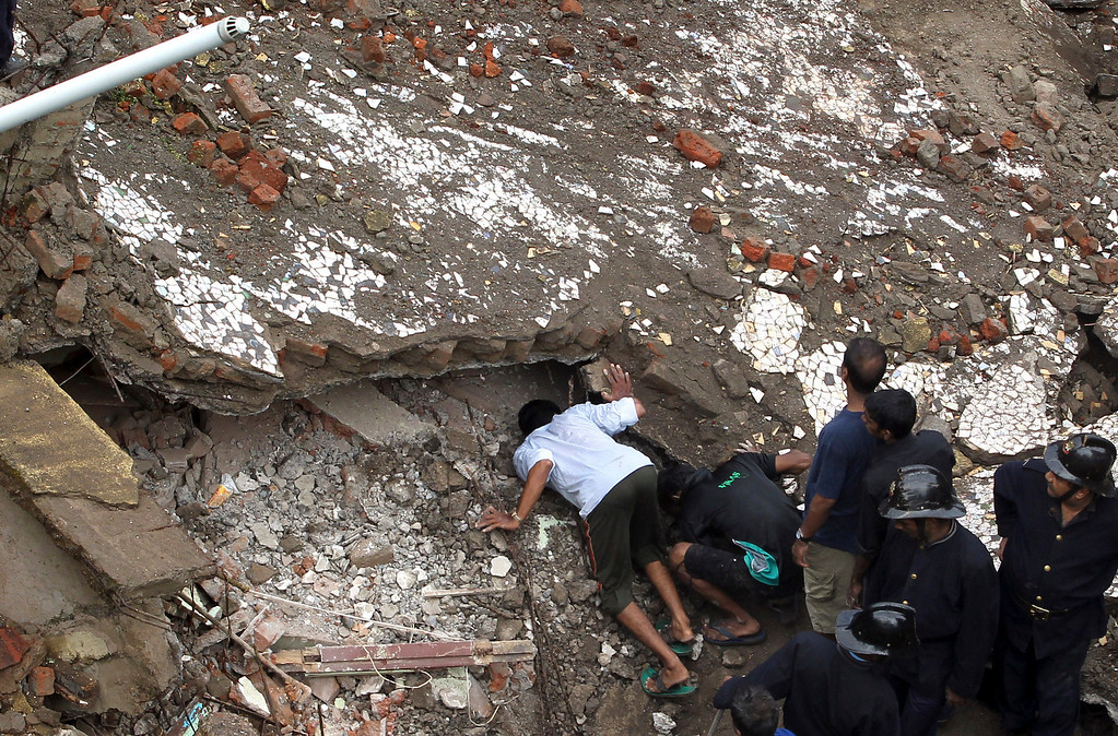 . A local and Indian Fire officials look for survivors from the debris of a collapsed building in Mumbai, India, Friday, Sept. 27, 2013.  (AP Photo/Rajanish Kakade)