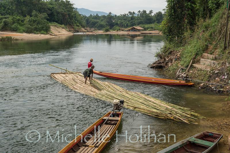 YE, MYANMAR - DECEMBER 9, 2018: Unidentified men float bamboo down river for sale.