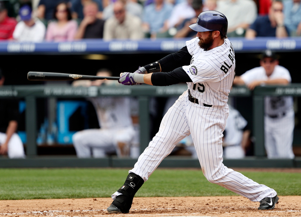 . Colorado Rockies\' Charlie Blackmon follows through with his swing after connecting for a solo home run against the San Francisco Giants in the fourth inning of a baseball game in Denver on Wednesday, April 23, 2014. (AP Photo/David Zalubowski)