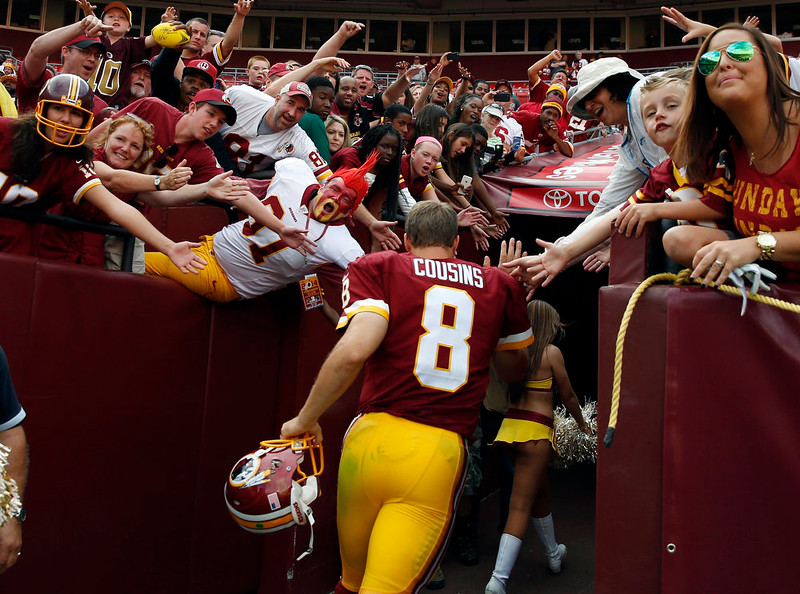 . Washington Redskins quarterback Kirk Cousins (8) runs off the field after an NFL football game against the Jacksonville Jaguars on Sunday, Sept. 14, 2014, in Landover, Md. The Redskins won 41-10. (AP Photo/Evan Vucci)