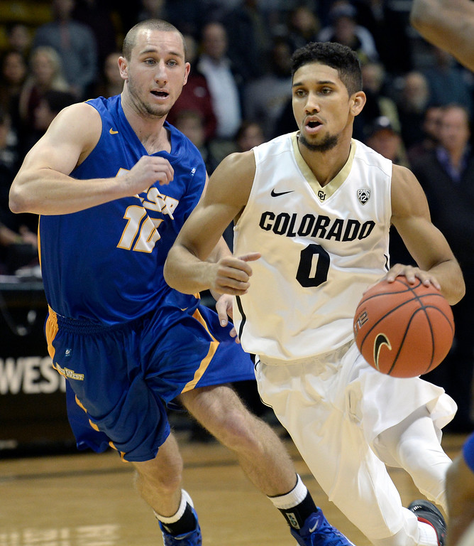. University of Colorado\'s Askia Booker drives the ball past Kyle Boswell during a game against  the University of California Santa Barbara, on Nov. 20, at the Coors Event Center in Boulder. (Jeremy Papasso/Boulder Daily Camera)