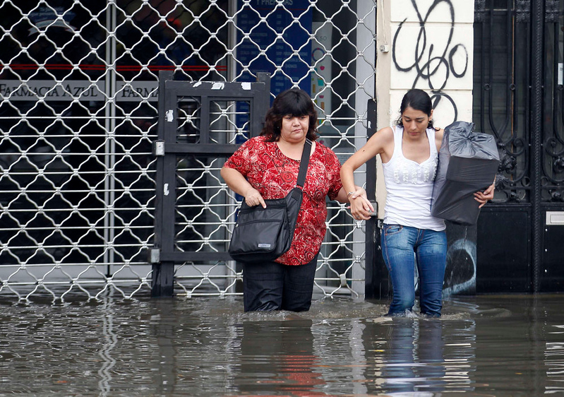 . People carry their belongings in a flooded street after a rainstorm in Buenos Aires April 2, 2013. Thunderstorms damaged property and vehicles, cut power and caused delays on flights in Buenos Aires and its suburbs. The City\'s SAME emergency service announced that the death toll has risen to five.  REUTERS/Enrique Marcarian