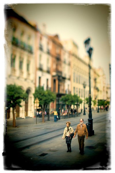 Elderly couple walking on Constitution Avenue, Seville, Spain. Taken with tilted lens to get shallower depth of field and digitally edited to look like an old print.