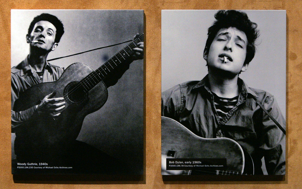 """. ** ADVANCE FOR WEEKEND EDITIONS NOV. 20-21 ** A photo of Woody Guthrie, from the 1940\'s, left, is displayed next to one of Bob Dylan, from the 1960\'s,   as part of a new display about Dylan at the Experience Music Project Wednesday, Nov. 17, 2004, at the museum in Seattle. The first major museum exhibit dedicated to Dylan\'s work, \""""Bob Dylan\'s American Journey, 1956-1966,\"""" opens there Saturday, Nov. 20. Dylan was greatly influenced by Guthrie and in many ways patterned himself after him. (AP Photo/ElaineThompson)"""