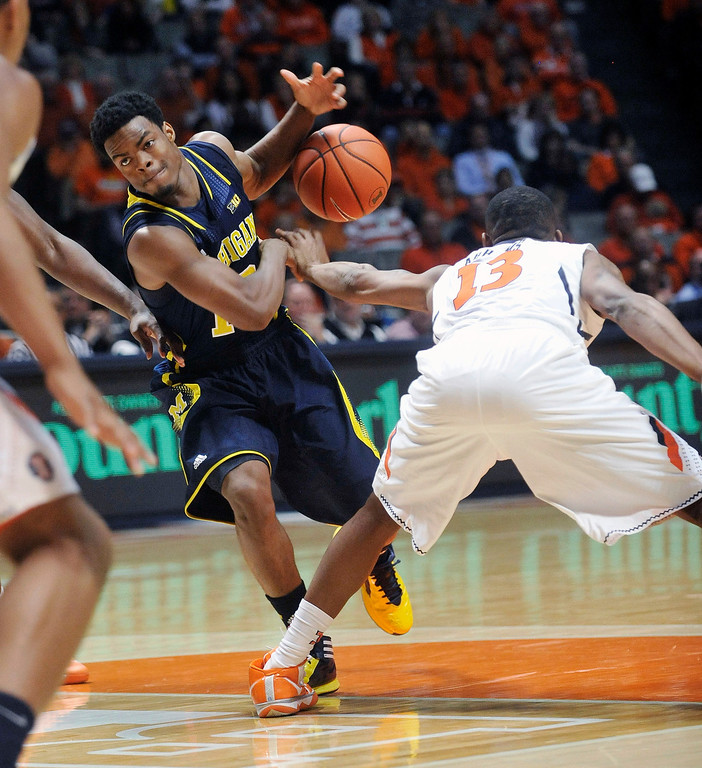 . Michigan guard Derrick Walton Jr. (10) has the ball stripped by Illinois guard Tracy Abrams (13) during the second half of an NCAA college basketball game Tuesday, March 4, 2014, in Champaign, Ill. Michigan won 84-53. (AP Photo/Rick Danzl)