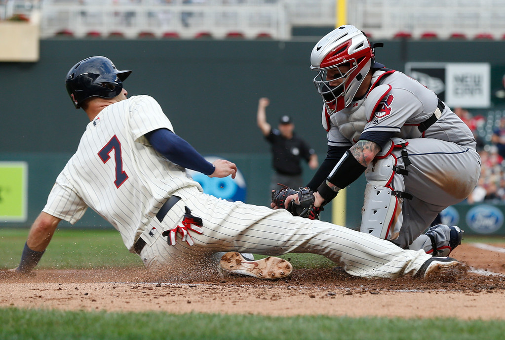 . Minnesota Twins\' Joe Mauer, left, is tagged out by Cleveland Indians catcher Roberto Perez for a double play in the third inning of the second game of a baseball doubleheader Thursday, Aug. 17, 2017, in Minneapolis. (AP Photo/Jim Mone)