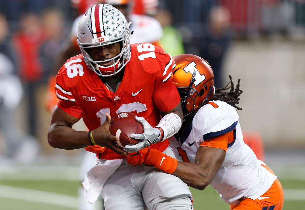 . Ohio State quarterback J.T. Barrett, left, carries Illinois defensive back Stanley Green into the end zone for a touchdown during the first half of an NCAA college football game Saturday, Nov. 18, 2017, in Columbus, Ohio. (AP Photo/Jay LaPrete)