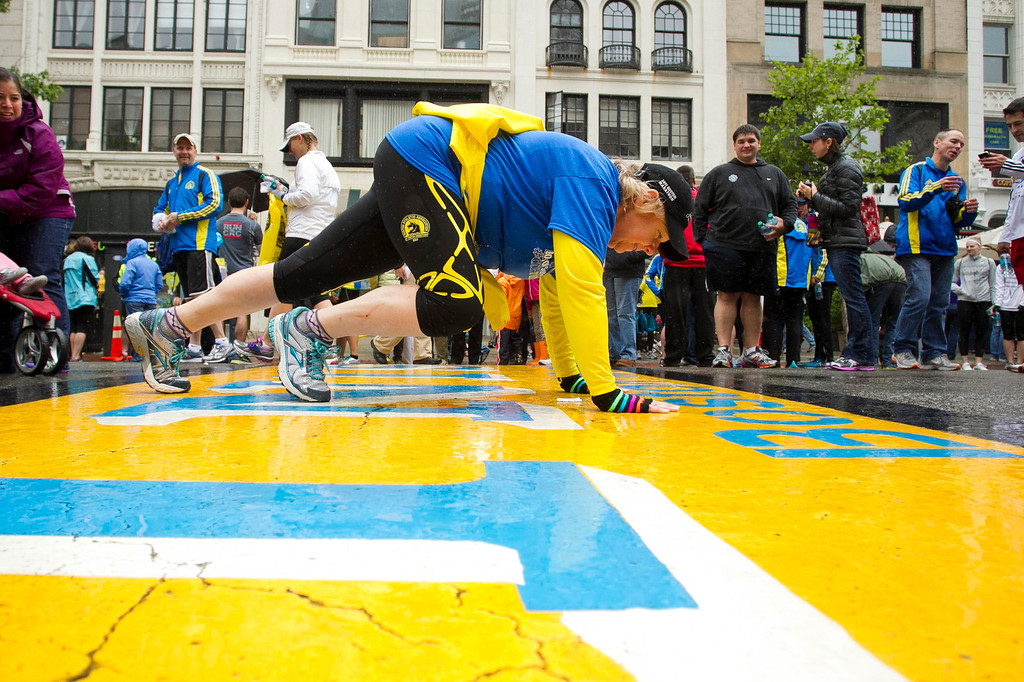 ". A runner does a plank as others cross the finish line after completing the final mile of the Boston Marathon course during ""#onerun\"" in Boston, Massachusetts, May 25, 2013.   REUTERS/Dominick Reuter"