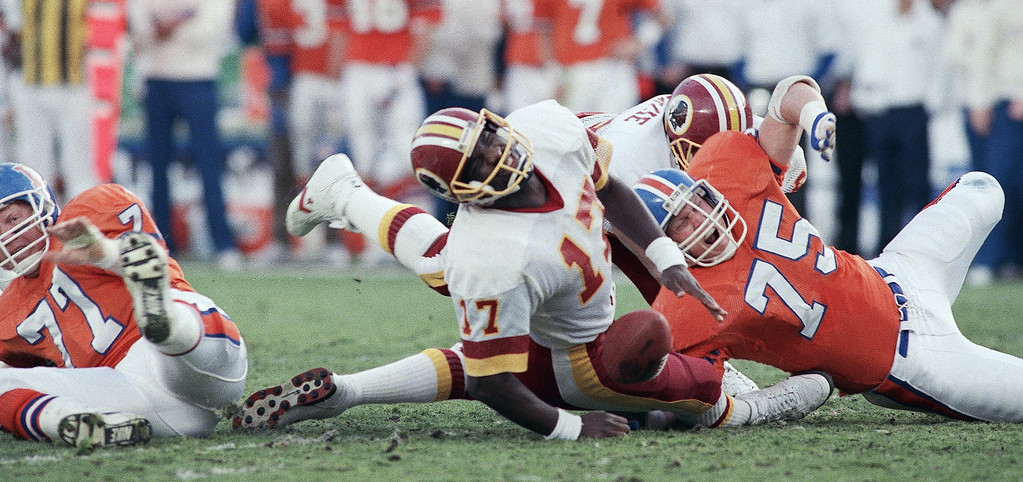 . Washington Redskins quarterback Doug Williams grimaces as he hits the ground in first quarter of Super Bowl XXII, Sunday, Jan. 31, 1988 in San Diego. Williams had a slight leg injury but returned to the game. At right is Denver Broncos defensive end Rulon Jones. (AP Photo/Rusty Kennedy)