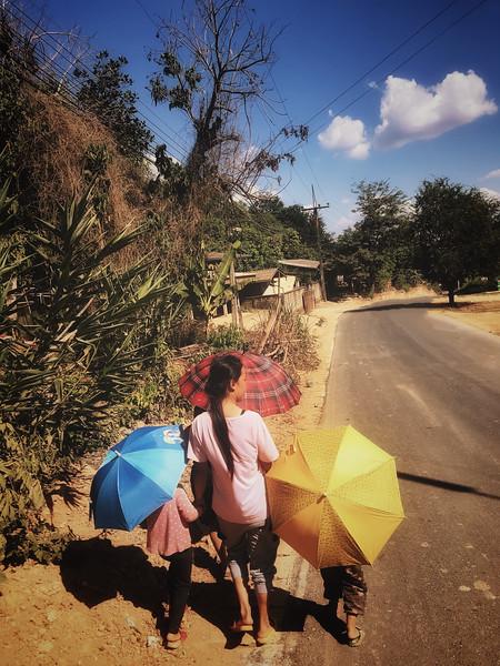 Hmong family walking through a Thai village