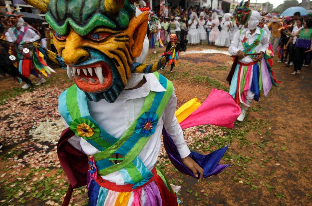 . Dancers wearing a traditional devil mask and costumes dance, in which the devils pay penance and ask for relief from physical ailments, symbolizes the ongoing struggle between good and evil, during Corpus Christi celebrations, in the streets of La Villa, Panama, Thursday, May 30, 2013. Residents don colorful masks and bright costumes as they dance through the streets of this small Panamanian town, for its annual commemoration of Corpus Christi, a Roman Catholic holiday celebrating the transformation of the body and blood of Christ into bread and wine. (AP Photo/Arnulfo Franco)