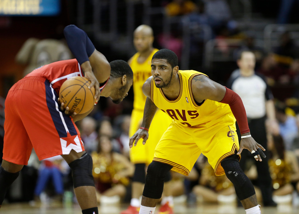 . Cleveland Cavaliers\' Kyrie Irving, right, defends Washington Wizards\' John Wall in an NBA basketball game Sunday, Feb. 23, 2014, in Cleveland. (AP Photo/Mark Duncan)